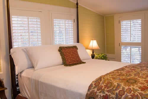 Soft yellow painted befroom with large four poster wooden bed with white linens and rust colored duvet and throw pillow with two windows