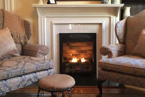 Two upholstered blue and cream arm chairs with small setee flanking white manteled wood burning fireplace