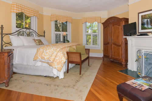 Large guestroom with soft orange walls, jute rug, large wooden armoire and large white bed with matching coverlet and white linens
