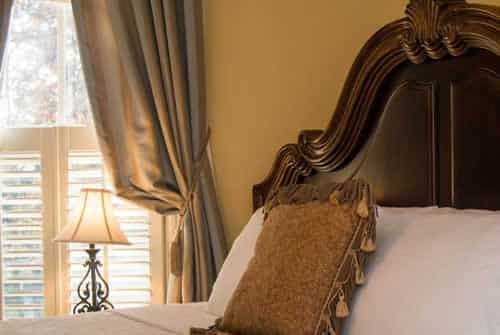 Cream painted room with large mahogany wood headboard, neutral colored drapes and white bed linens and soft rose colored throw pillow