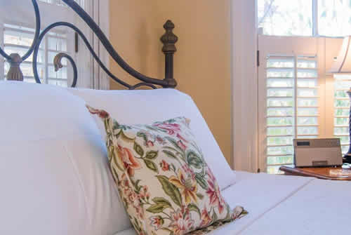 Soft orange walls with black cast iron bed with white linens and floral throw pillow