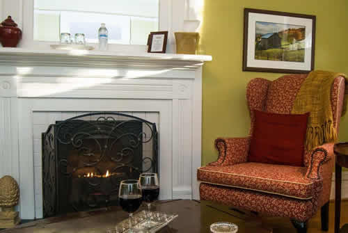 Close up view of cranberry arm chair next to fireplace with cast iron front and white mantel surround