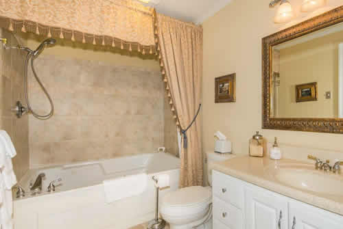 Tan tiled bathroom with large white ceramic tub with soft neutral shower curtain, white commode and vanity with mirror above