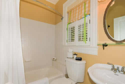 Soft orange painted walls with white tiled bathroom with tub, pedestal sink and white trimed window