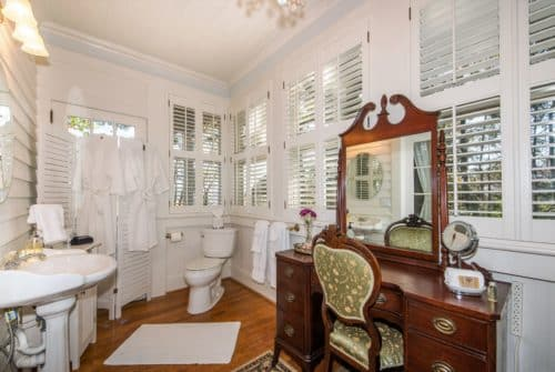 Bathroom with white planked wood floors, white walls with large windos, claw foot tup and dark wood make up table and mirror