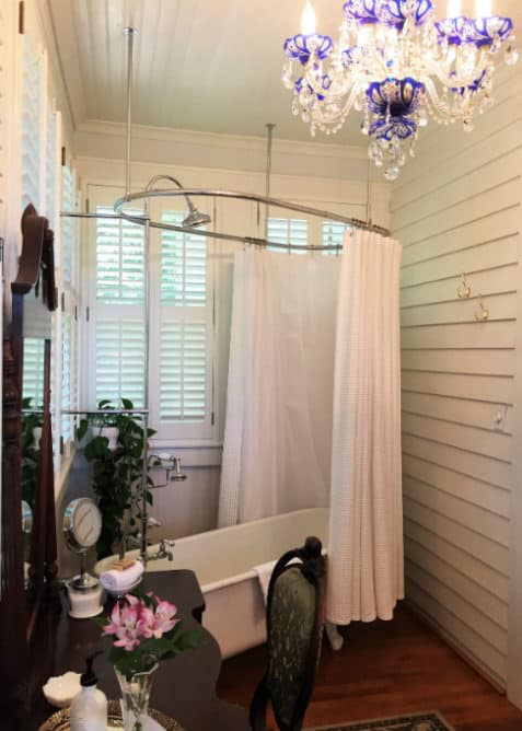 White clawfoot tub with white shower curtain in front of white shuttered windows