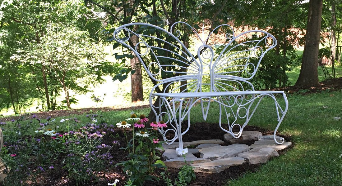 White cast iron butterfly shaped garden bench on small stone patio surrounded by greenery