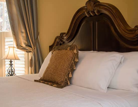 bedroom with mahogany headboard white beadspread and gold pillow and drapes