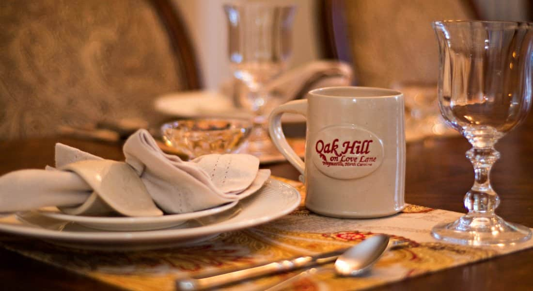 Large white plate with service plate on top with fleur de lis folded white napkin, white coffee mug with inn  logo in red and tall water glass on tan placemat