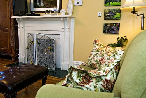 White manteld fireplace in soft yellow painted room, soft green plush loveseat and multi colored pillows