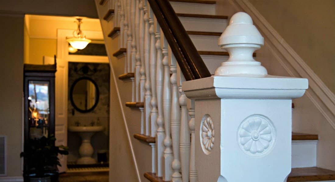 White painted grand wood stair bannister with natural wood rail facing powder room