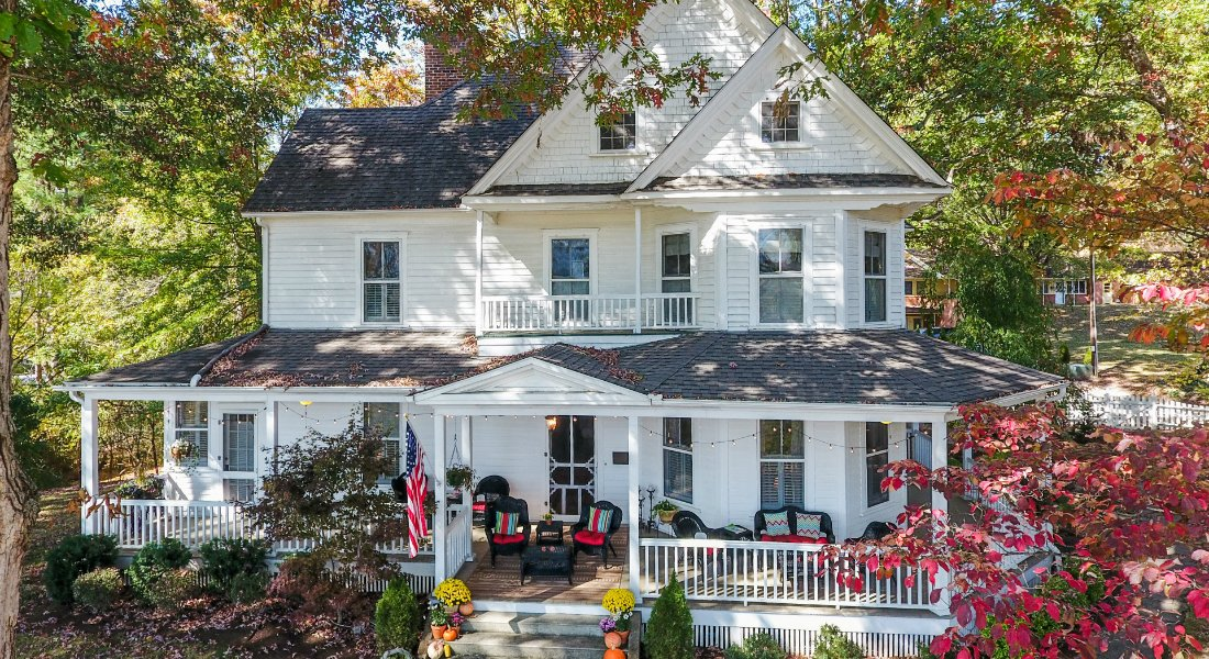Three story white colonial house with large covered front porch surrounded by tall greet trees and red fall colored smaller tree leaves
