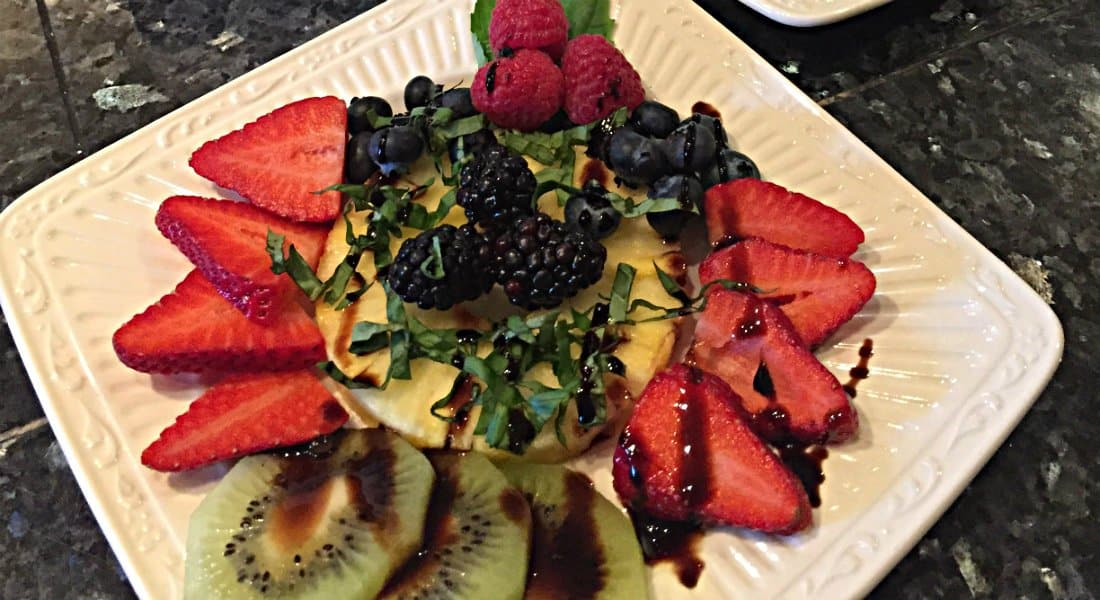 White plate of nicely displayed fresh strawberries, kiwi and pinapple with sayayon sause and green garnish