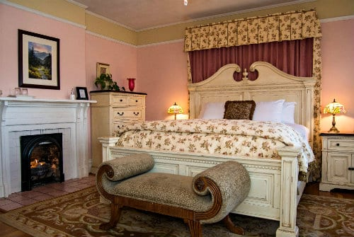Grand white wood bed with burgundy upholstery behind head board, white linens and matching coverlet