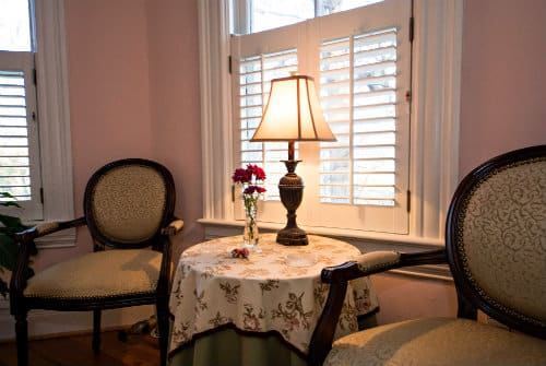 Two dark wood arm chairs on each side of small table with white linen and small table lamp in front of window
