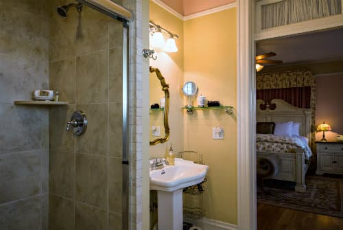Soft yellow bathroom with white pedestal sink and glass front walk in shower