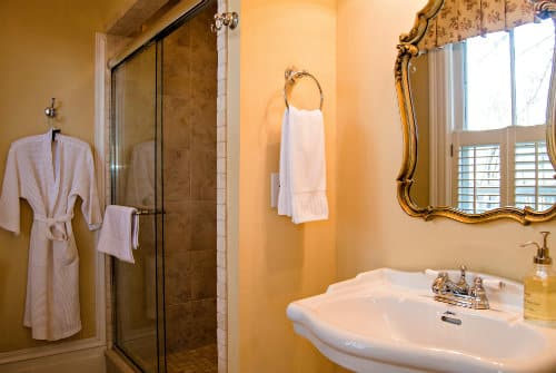 Soft orange painted wall with white pedestal sink, wood mirror above, white hand towel and glass standing shower