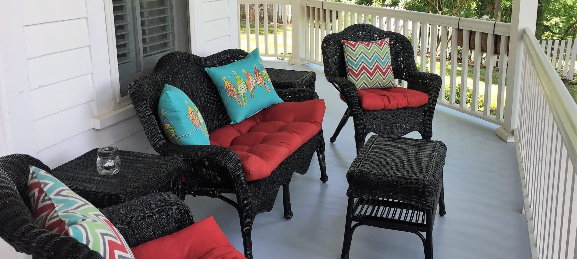 Dark wicker chairs and loveseat with small table with red cusions and vibrant bule and green pillows on outdoor front porch