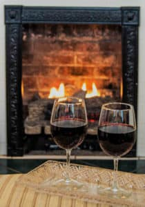 two glasses of red wine in front of a fireplace with roaring fire with cast iron surround