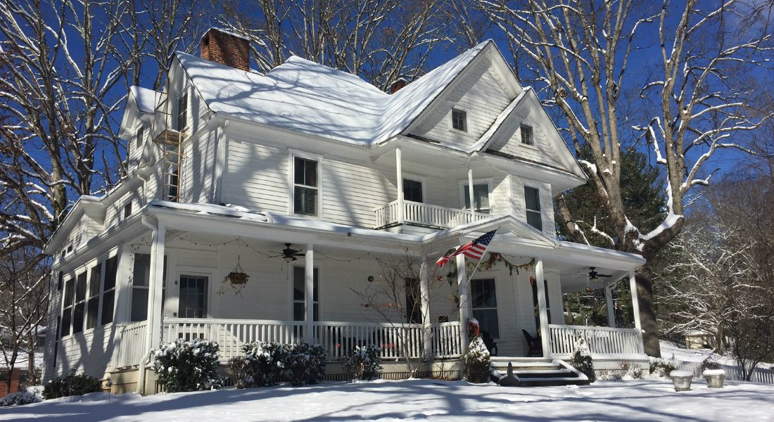 Winter scene of snow covered three story white colonial house with large covered front porch and American flag out front