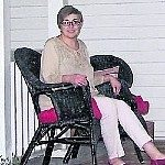 Anna in white pants in top sitting in dark wicker chair with red cusions on front covered porch