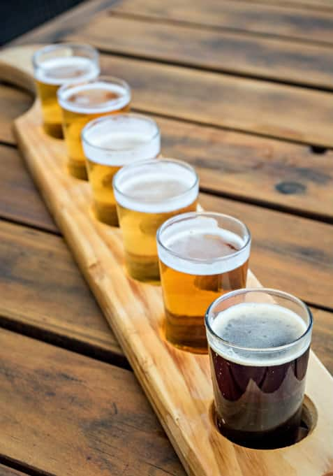 Flight of dark to light colored beers on dark wood table