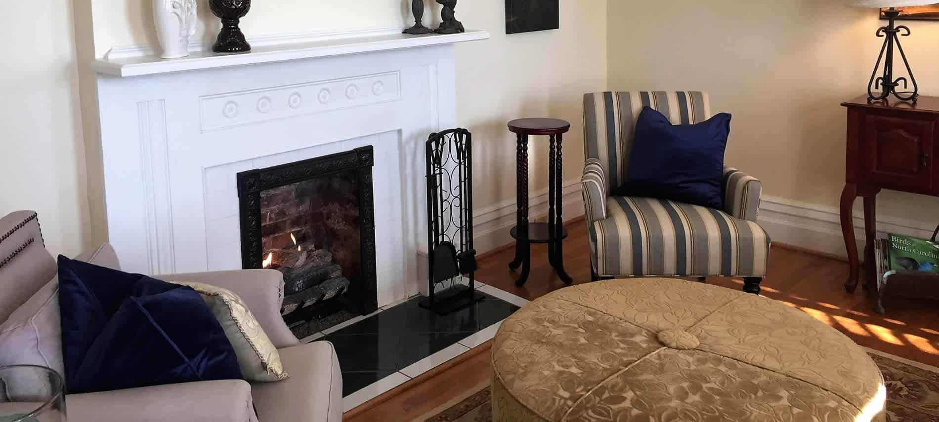 Beige sitting room with tan ottoman, two blue and beige upholstered chairs flanking a fireplace with white wraparound mantel