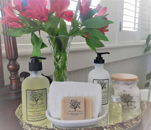 Close-up view of metal vanity tray with soaps and toiletries and vase of bright pink flowers