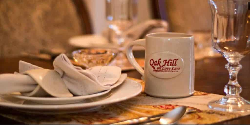 A table setting of white plates and napkins with a ceramic Oak Hill on Love Lane mug.