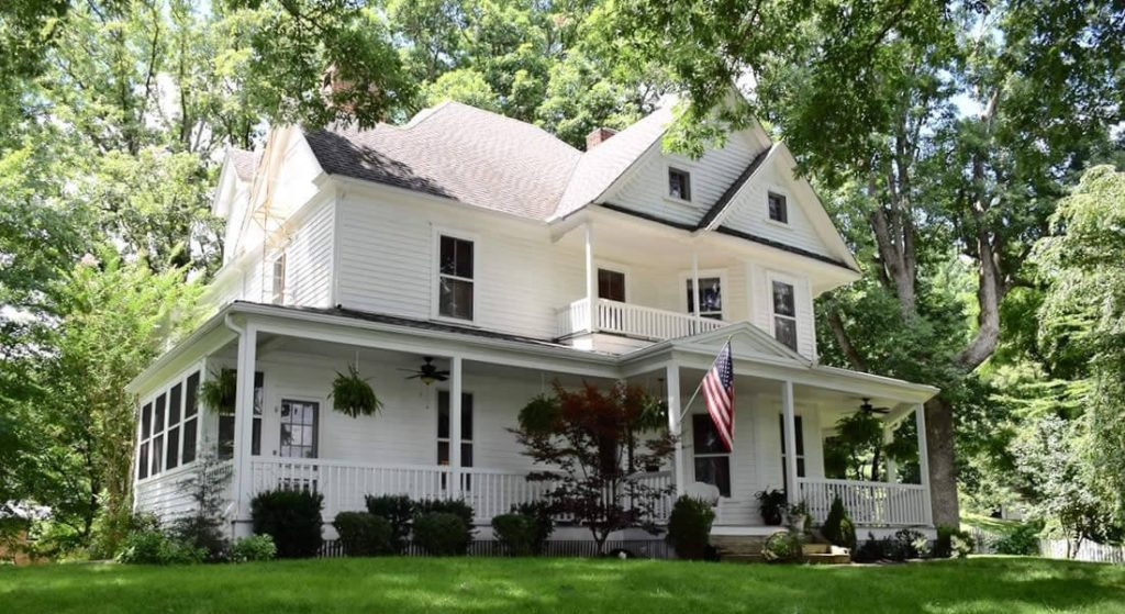 A large, white Victorian home with a wrap-around porch, surrounded by green trees.
