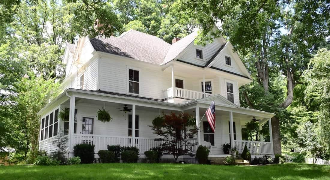 Three story white colonial house with large covered front porch surrounded by tall greet trees and American flag out front
