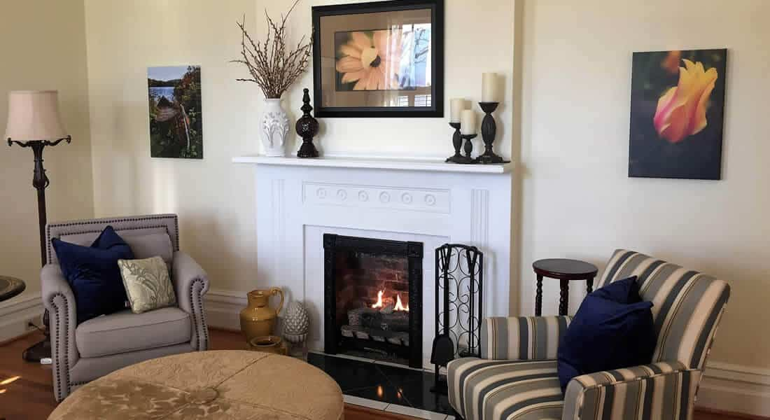 Cream colored wall sitting room with large fire place with white wood paneled mantle and surround flanked by one striped wingback chair and one gray one.