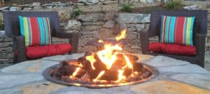 Two dark wicker chairs with colorful striped cushions around a circular stone fire pit and warm fire
