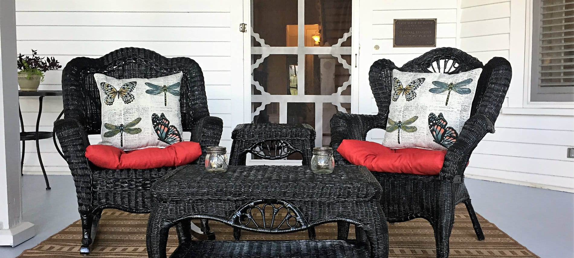 Two dark wicker chairs with coffee table and side table, red cushions and white pillows with dragonflies in front of screen door