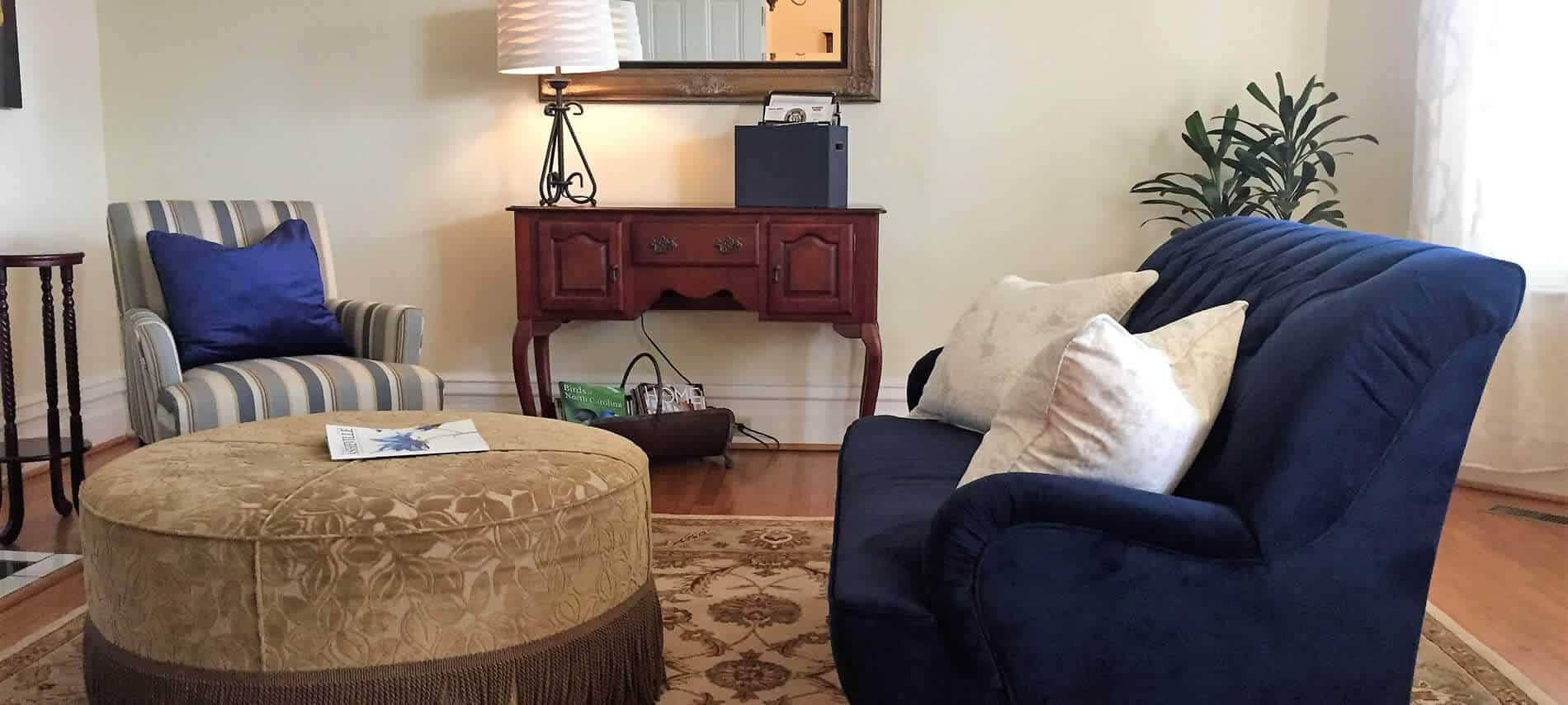 Sitting area with hardwood floors, blue and beige furniture, gold ottoman and wood console table with lamp and mirror