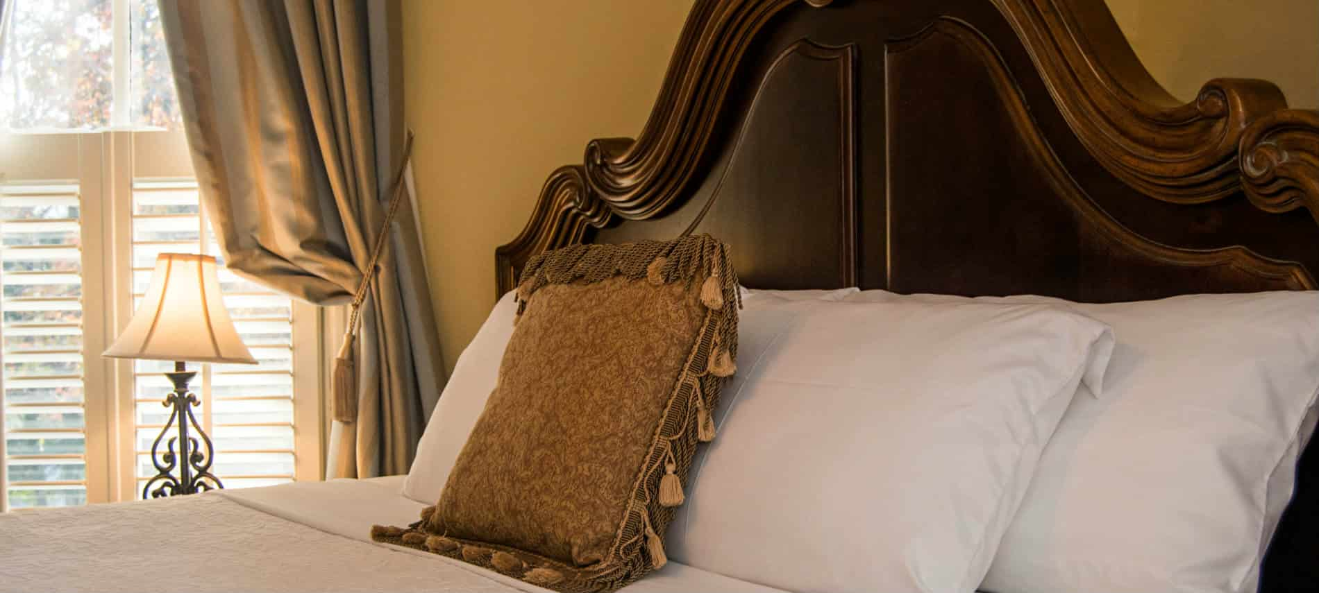 Soft yellow painted room with grand dark wood ornate headboard, white linens, gold and bronze throw pillow in front of curtained window