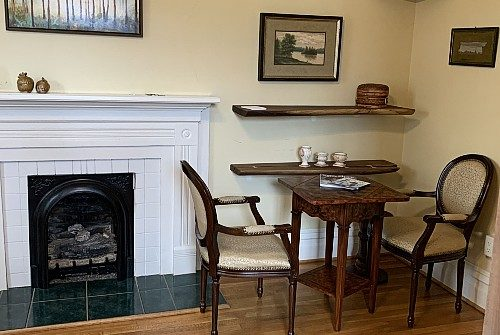Soft yellow room with warm wood floors, white painted surround mantel with fireplace next to two wood and upolstery covered chairs and wood table