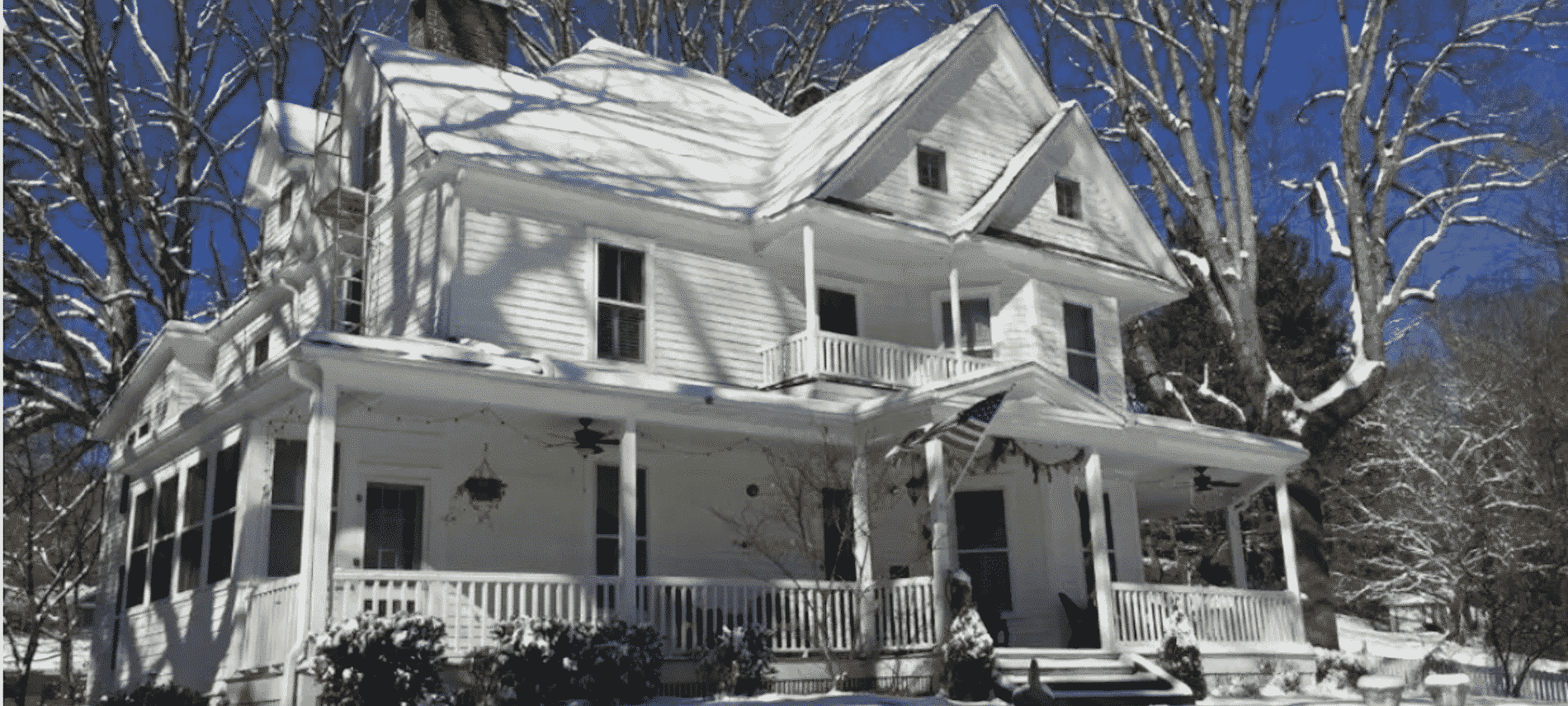 Exterior front view of Oak Hill on Love Lane, white traditional two-story home topped with fresh snow