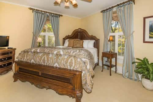 Beige bedroom with wood headboard and footboard, blue and tan curtains, nightstands with lamps, and green plant