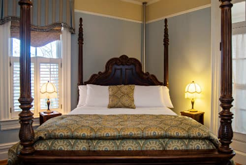 Soft blue painted guestroom with large dark wood four poster bed with natural colored duvet and pillows, white linens, next to windo