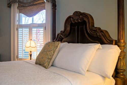 Large dark wood headboard of four poster bed with white linens next to window with natural light