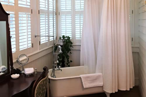 White claw foot tub with shower handle, white shower curtain in front of white shuttered windows