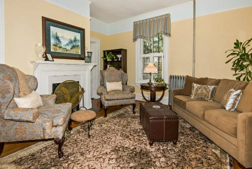 Yellow painted guestroom sitting area with couch, large blue upholstered arm chair and neutral oriental rug
