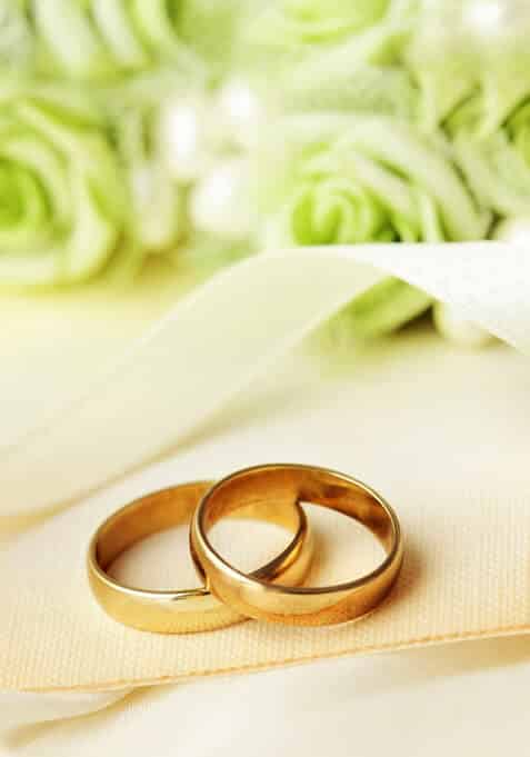 Up close view of two simple gold weddings bands laying on top of one another on cream tablecloth and white roses in background.