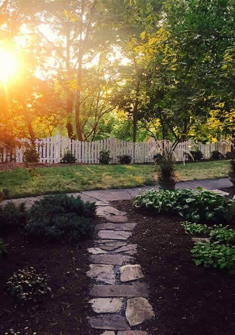Stone footpath through dark brown mulch with the sun peeking through the trees in the background