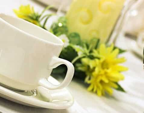 White coffee cup and saucer on white table linen and silver cuttlery in front of soft yellow candle and hurricaine globe and yellow daisy