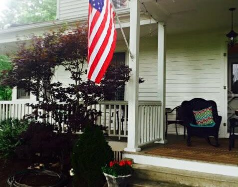 Front facade of white colonial inn with front porch and American flag