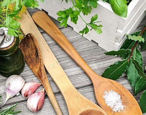 Two large wooden spoons with red and white spices on gray wood table next to gloves of garlic and white box with greens for cooking