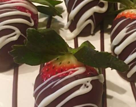 Four dark chocolate dipped red strawberries with white chocolate drizzled over top on white plate