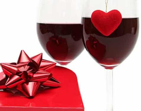 Two wineglasses with red wine and red heart on glass next to red heart shaped box of chololates with red bow on top